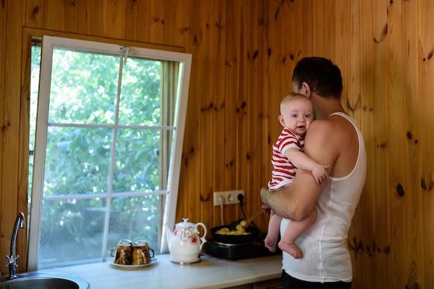 Vater mit einem kleinen baby in seinen armen kocht abendessen. innenraum eines landhauses Premium Fotos