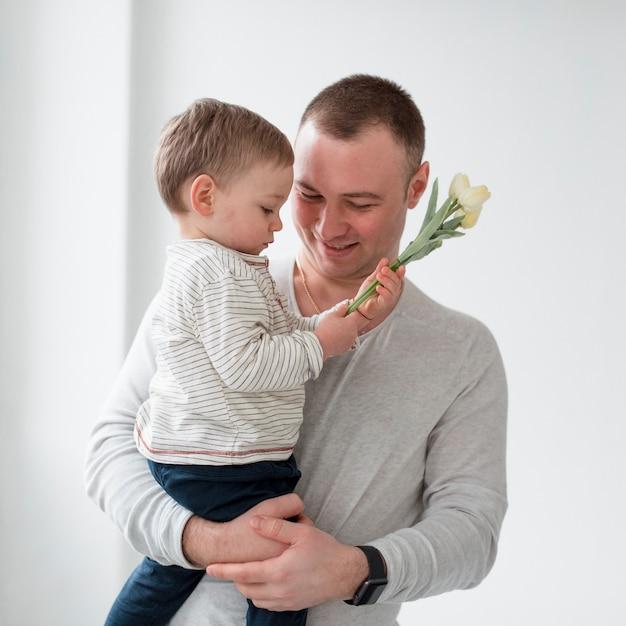 Vater mit kind, das blume hält Kostenlose Fotos