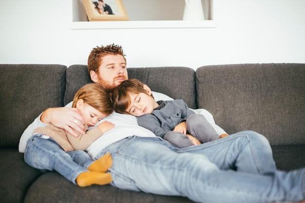 Vater mit nickerchen machenden söhnen auf sofa Kostenlose Fotos