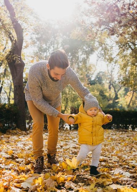 Vater mit seinem baby draußen in der natur Kostenlose Fotos