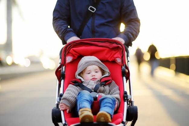 Vater mit seinem kleinen sohn im kinderwagen spazieren Premium Fotos