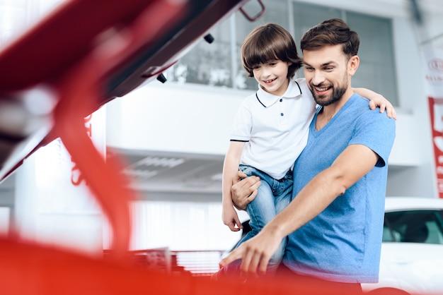 Vater mit seinem sohn in den armen in der kabine von neuwagen. Premium Fotos