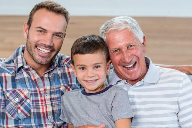 Vater, sohn und enkel sitzen auf dem sofa Premium Fotos