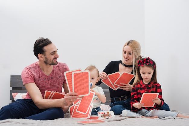 Vater spielt karten mit der familie Kostenlose Fotos