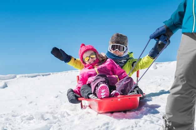 Vater spielt mit kindern auf schnee Premium Fotos