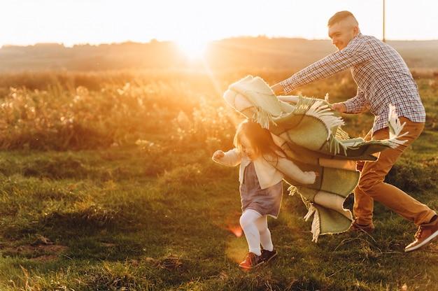 Vater spielt mit seiner kleinen Tochter auf dem grünen Gebiet bei Sonnenuntergang Premium Fotos