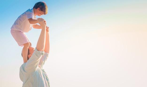 Vater trägt seinen fröhlichen sohn auf seinen schultern mit dem hellen himmel Kostenlose Fotos