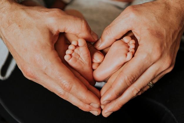 Vater und baby, die eine herzform bilden Kostenlose Fotos