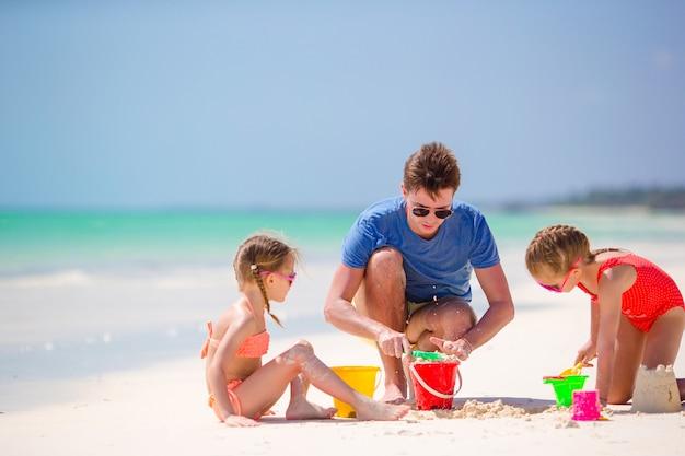 Vater und kinder, die sandburg am tropischen strand machen. familie, die mit strandspielwaren spielt Premium Fotos