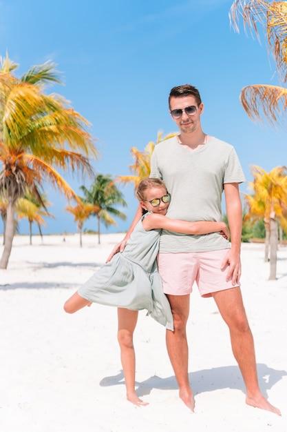 Vater und kleine mädchen haben viel spaß am weißen sandstrand Premium Fotos