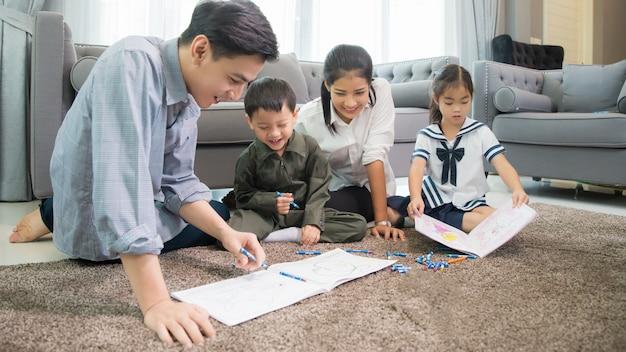 Vater und mutter bringen kindern bei, ihre hausaufgaben zu hause zu machen Premium Fotos
