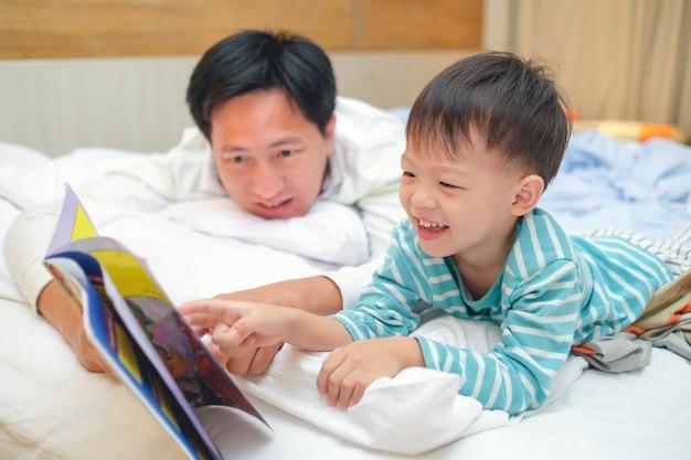 Vater und nettes kleines asiatisches kleinkindjungenkind, die schlafenszeitgeschichtenbuch lesen Premium Fotos