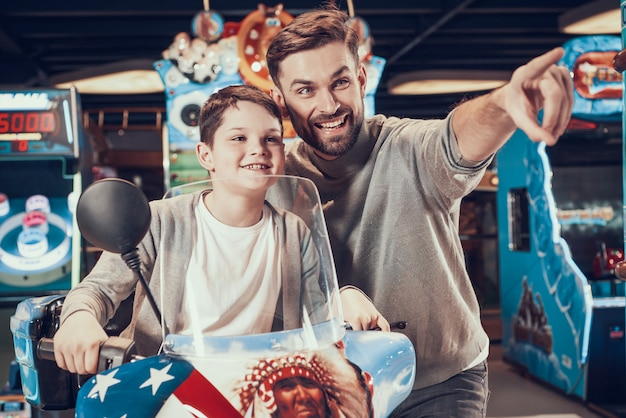 Vater und sohn auf dem spielzeugmotorrad, das vorwärts schaut Premium Fotos