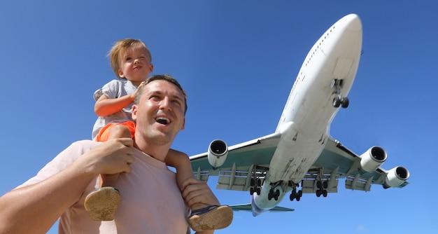 Vater und sohn beobachten das landungsflugzeug Premium Fotos