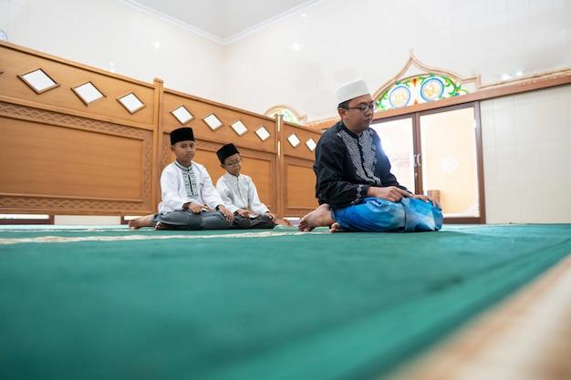Vater und sohn beten zusammen in der moschee Premium Fotos