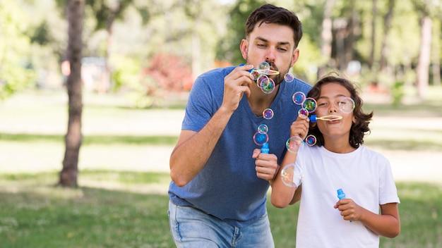Vater und sohn blasen im park blasen zusammen | Premium-Foto