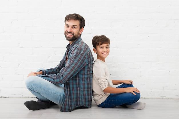 Vater und sohn, die auf boden sitzen und fotografen betrachten Kostenlose Fotos