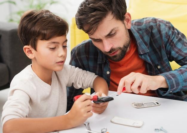 Vater und sohn, die ein telefon reparieren Kostenlose Fotos