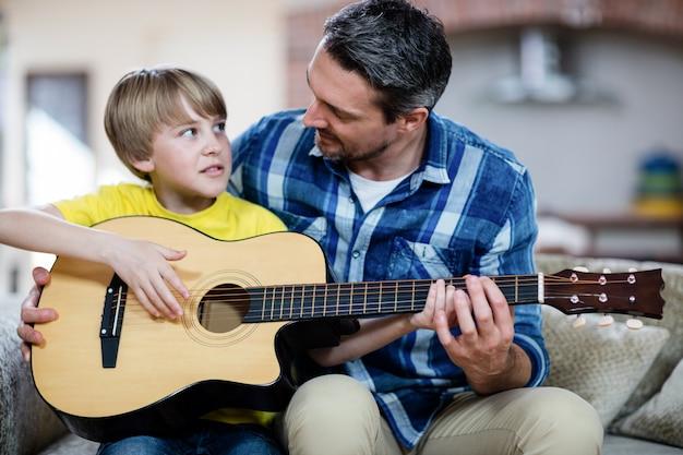 Vater und sohn, die eine gitarre spielen Premium Fotos