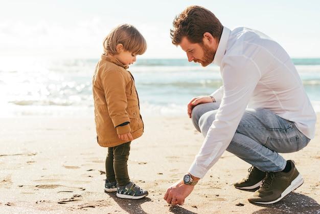 Vater und sohn, die kiesel aufheben Kostenlose Fotos