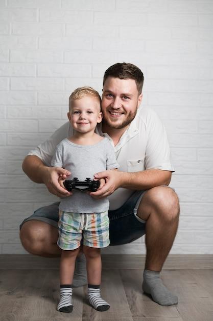 Vater und sohn, die zu hause mit steuerknüppel spielen Kostenlose Fotos