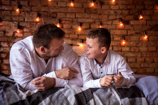 Vater und sohn, die zu hause reden, liegen im bett Premium Fotos