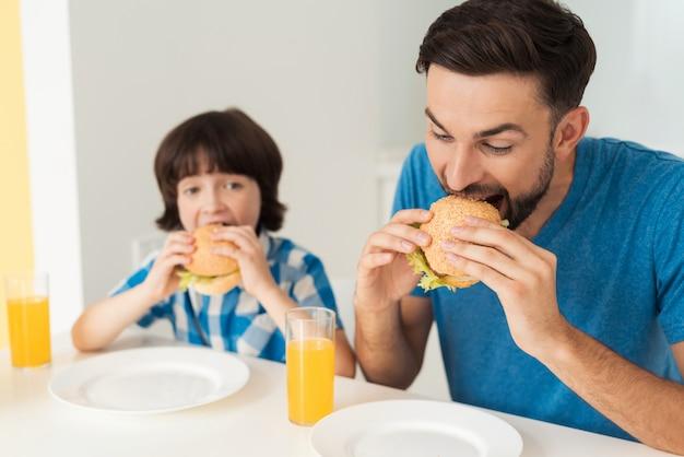 Vater und sohn essen einen hamburger mit saft. Premium Fotos
