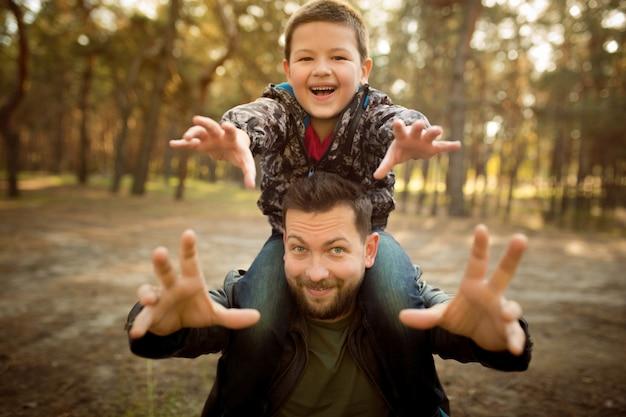 Vater und sohn gehen spazieren und haben spaß im herbstwald, sehen glücklich und aufrichtig aus Kostenlose Fotos