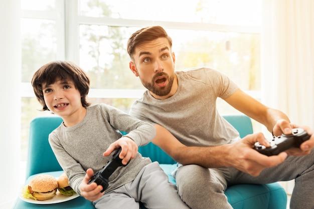 Vater und sohn sitzen und spielen auf der konsole. Premium Fotos