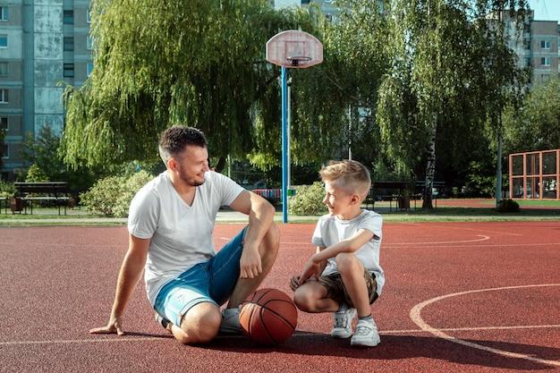 Vater und sohn spielen gemeinsam basketball auf dem basketballplatz Premium Fotos