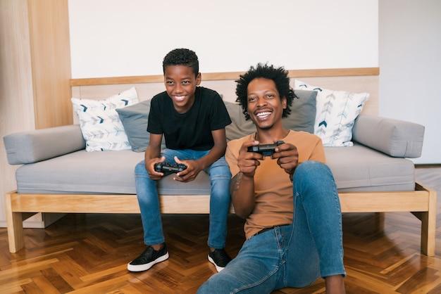 Vater und sohn spielen zu hause zusammen videospiele. Premium Fotos