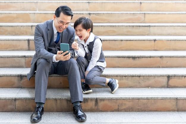 Vater und sohn spielen zusammen smartphone auf geschäftsviertel urban Kostenlose Fotos