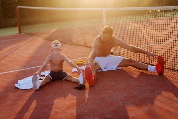 Vater und sohn trainieren zusammen. auf dem trainingsfeld sitzen und sich nach starkem regen dehnen. gemeinsam spaß haben. Premium Fotos