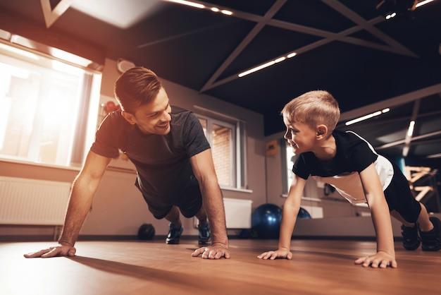 Vater und sohn tun push-ups in der turnhalle. Premium Fotos