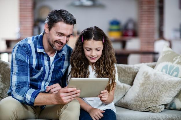 Vater und tochter, die digitale tablette im wohnzimmer verwendet Premium Fotos