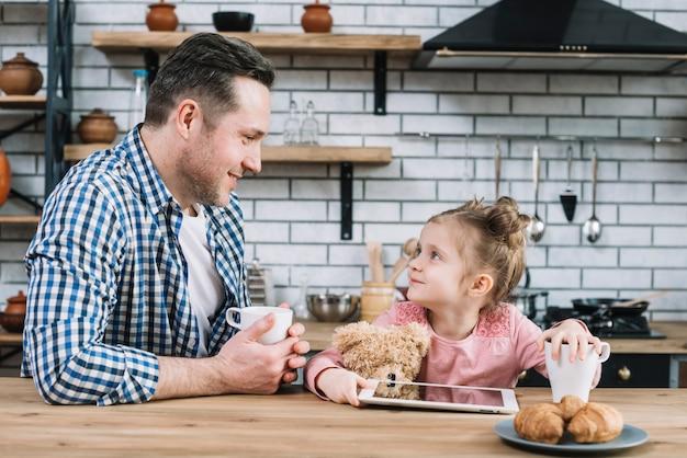 Vater und tochter, die einander beim trinken des kaffees in der küche betrachten Kostenlose Fotos