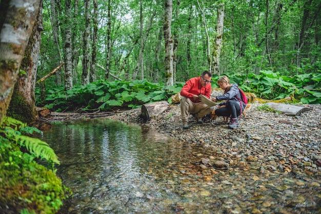 Vater und tochter, die im wald wandern und karte überprüfen Premium Fotos
