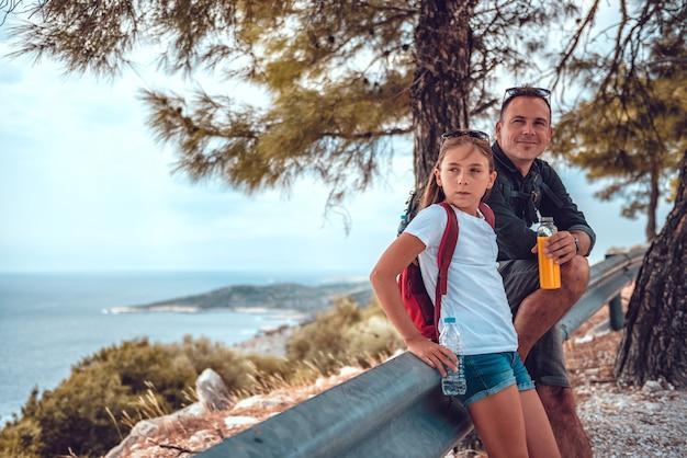 Vater und tochter, die nach dem wandern entlang seeküstenlinie stillstehen Premium Fotos