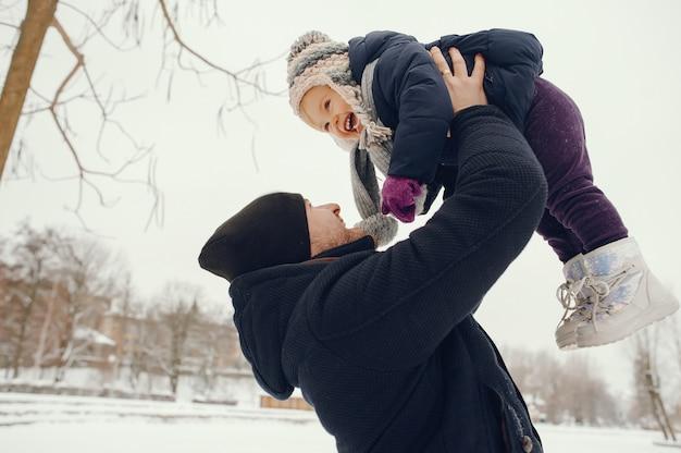 Vater und tochter in einem winterpark Kostenlose Fotos