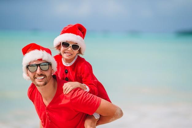 Vater und tochter in santa hat haben spaß am tropischen strand Premium Fotos