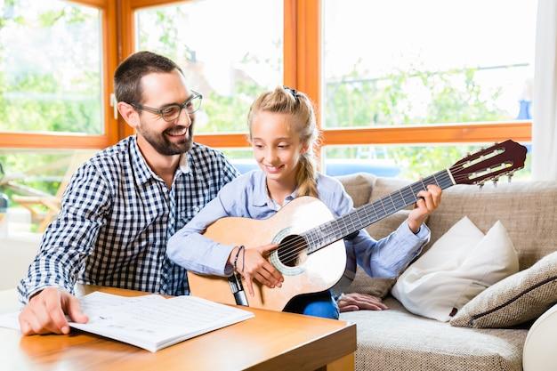 Vater und tochter lernen gitarre zu spielen Premium Fotos