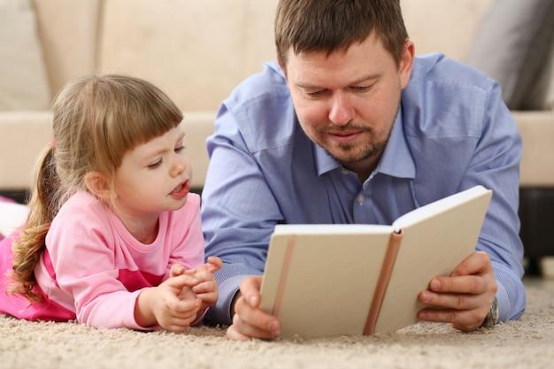 Vater und tochter liegen auf dem boden und lesen zusammen ein interessantes buch Premium Fotos