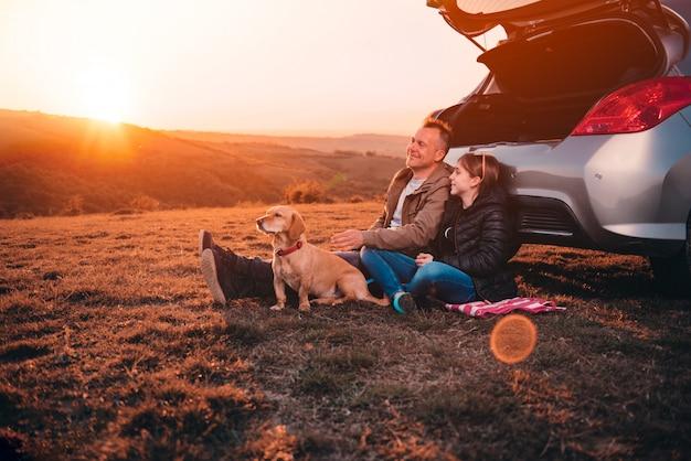 Vater und tochter mit dem hund, der auf einem hügel durch das auto während des sonnenuntergangs kampiert Premium Fotos