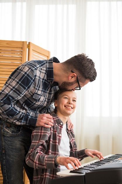 Vater und tochter spielen am klavier Kostenlose Fotos