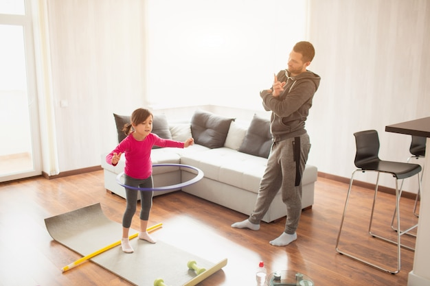 Vater und tochter trainieren zu hause. training in der wohnung. sport zu hause. sie dreht einen hula hoop und papa misst die zeit mit einer sportuhr Premium Fotos