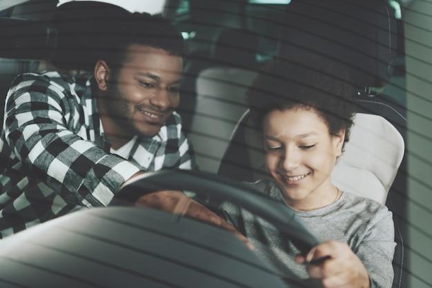 Vater unterrichtet den kleinen sohn, der familie im auto fährt Premium Fotos