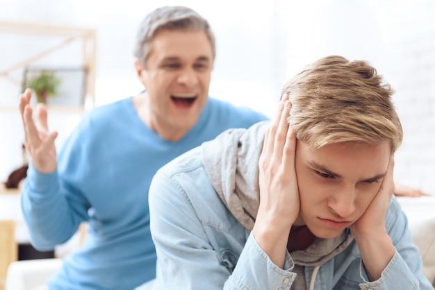 Vater versucht zu reden, aber sohn schließt die ohren Premium Fotos