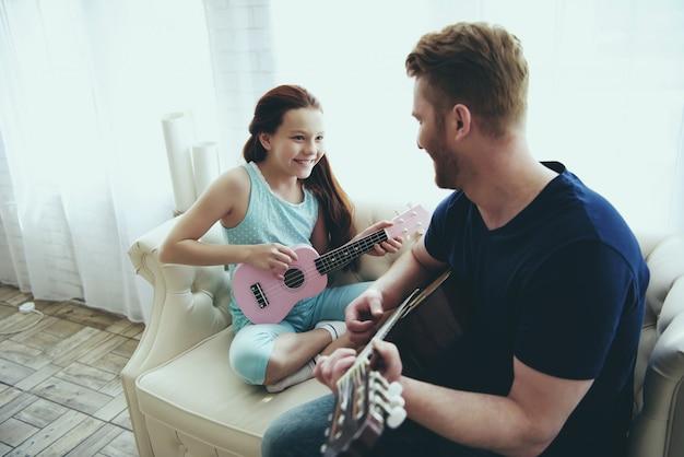 Vater zeigt tochter, wie man gitarre spielt. Premium Fotos