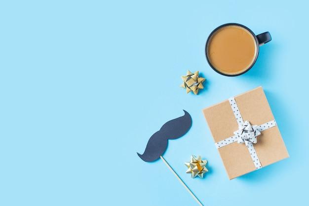 Vatertagskonzept mit geschenkbox, bindung und dem schnurrbart auf blauem hintergrund Premium Fotos