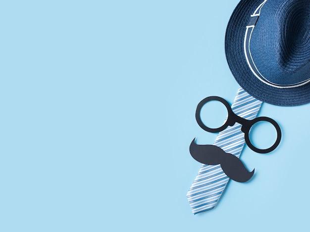 Vatertagskonzept mit hut, gläsern und bindung auf blauem hintergrund Premium Fotos